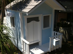 Country Cubby House with 3 open windows with hoods, saloon doors, veranda and mailbox.